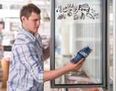Young handsome man thinking of healthy food while shopping at grocery store — Stock Photo
