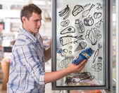 Young handsome man thinking of healthy food while shopping at grocery store — Foto Stock