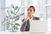 Concept of Growing company with sketch of a plant with business symbols and businesswoman working on laptop — Stock Photo