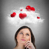 Red hearts flying in cloud overhead of beautiful dreamy woman. — Stock Photo