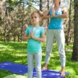 Stock Photo: Mother and daughter doing exercise outdoors