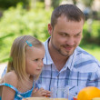 Family eating together outdoors at summer park or backyard — Stockfoto