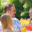 Family eating together outdoors at summer park or backyard — Stok fotoğraf