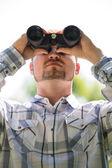 Man with Binoculars outdoors — Stock fotografie