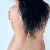 Unrecognizable brunette lady on gray background — Stock Photo