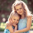Outdoor portrait of two embracing cute little girls — Stock Photo #44970447