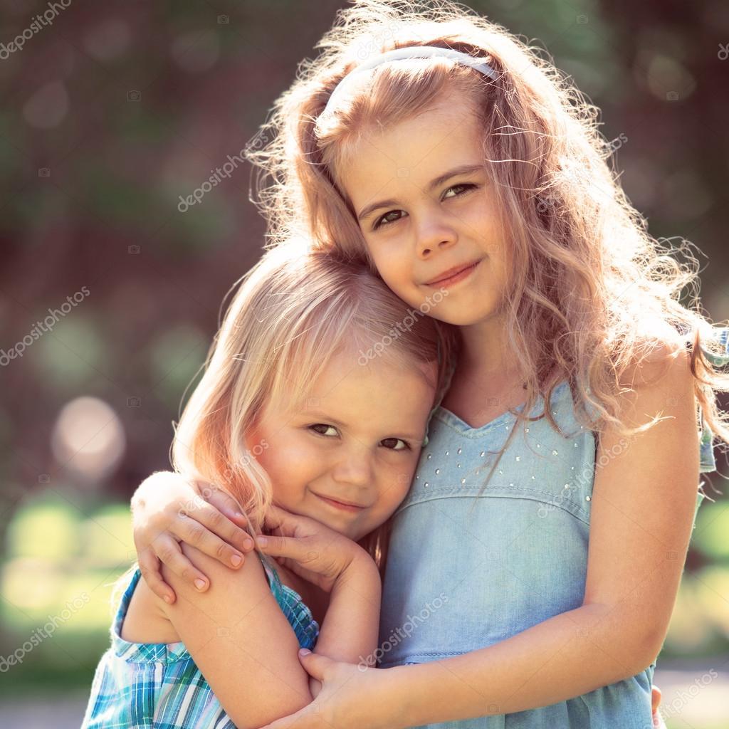маленькие девочки Открытый Портрет двух обнимая милые маленькие девочки – Стоковое изображение