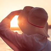 Mladá a krásná žena nosí klobouk v západu slunce světlo hledá — Stock fotografie