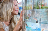 Woman selecting tv channel glass touch screen — Stock Photo