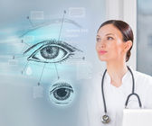 Doctor working virtual interface examining human eye — Stock Photo