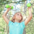 Happy little girl lifting dumbbells in park outdoors — Stock Photo #46534577