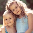 Outdoor portrait of two embracing cute little girls — Stock Photo #46534939