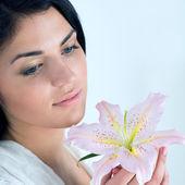 Jonge vrouw genieten van lily bloem geur — Stockfoto