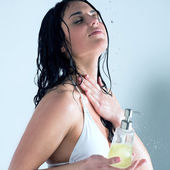Beautiful girl showering. Holding glass bottle with shower gel — Stock Photo
