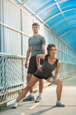 Athletic couple pumping up muscles — Stock Photo