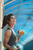 Athletic woman pumping up muscles — Stock Photo