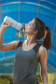 Woman drinking water sweating exercising — Stock Photo