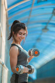 Woman pumping up muscles with dumbbells — Stock Photo