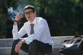 Business man smoking — Stock Photo