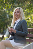 Businesswoman typing on smartphone — Stock Photo