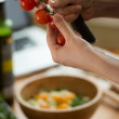 Hands holding and cutting cherry tomato — Stock Photo