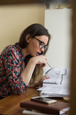 Woman working with blueprints at home — Stock Photo
