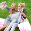 Portrait of two women relaxing on green grass after shopping. Ho — Stock Photo #6072382