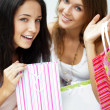 Two excited shopping woman resting on bench at shopping mall loo — Stock Photo #6567753