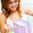 Photo of young joyful woman with shopping bags on the background — Stock Photo #7289334
