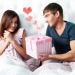 Happy young couple relaxing on a bed — Stock Photo #8660676