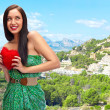 Cute young woman holds a heart symbol outdoors at beautiful view — Stock Photo #8984085