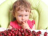 Child tastes cherry — Stock Photo