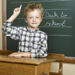 Stock Photo: Cheerful smiling child at blackboard. School concept