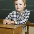 Portrait of cute boy front of a blackboard. — Stock Photo