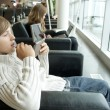 Young boy playing with a console in airport — Stock Photo