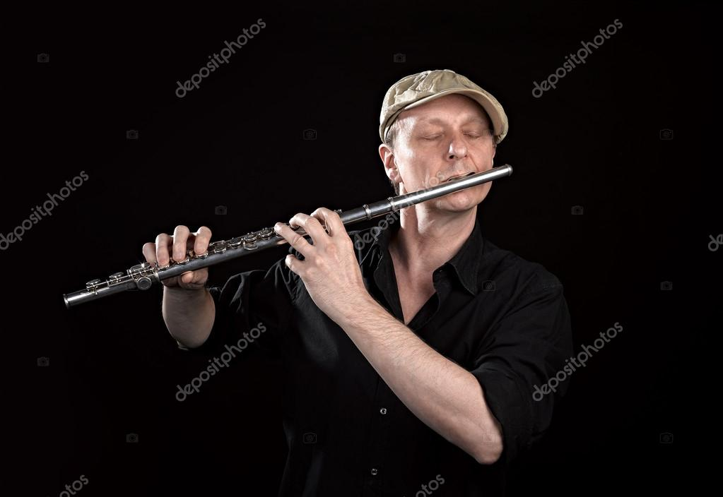 Portrait of a man playing old silver transverse flute on black background — Stock Photo #12768207