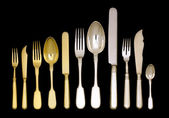 Old vintage silverware and goldenware set on black — Stock Photo