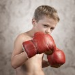 Non Aggressive child wearing boxing gloves on textured backgroun — Stock Photo