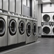 Row of industrial washing machines in public laundromat — Stock Photo #16980323