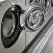 A row of industrial washing machines in a public laundromat - Foto de Stock