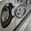 Stock Photo: Row of industrial washing machines in public laundromat