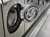 A row of industrial washing machines in a public laundromat — Foto Stock