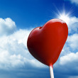 Heart-shaped lollipop on blue sky — Stock Photo