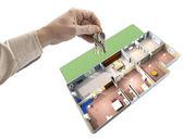 Mão segurando as chaves, mapa da casa no fundo — Fotografia Stock