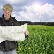 Photographer hiker with map against fields and nature — Stock Photo