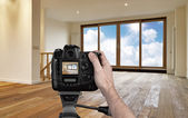 Man photographing empty living room with digital camera — Stock Photo