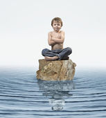 Zen Kid on rock in water — Stockfoto