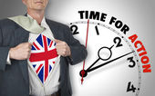 Businessman showing shirt with flag from UK suit against clock — Stock Photo