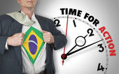 Businessman showing shirt with flag from Brazil suit against clo — Stock Photo