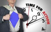Businessman showing superhero suit against clock — Stock Photo